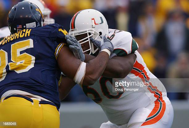 Offensive lineman Vernon Carey of the University of Miami Hurricanes is blocked by defensive tackle David Upchurch of the West Virginia University...