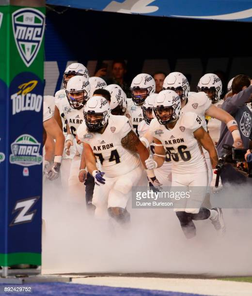 Offensive lineman Xavier Quigley of the Akron Zips leads the team onto the field before a game against the Toledo Rockets at Ford Field on December 2...