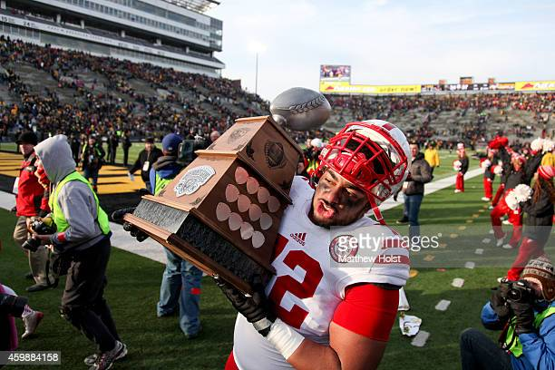 Offensive lineman Zach Hannon of the Nebraska Cornhuskers carries the Heroes Trophy off the field after the matchup against the Iowa Hawkeyes on...