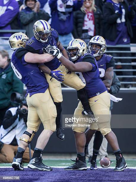 Offensive linemen Kaleb McGary left of the Washington Huskies and Andrew Kirkland of the Washington Huskies lift wide receiver Chico McClatcher after...