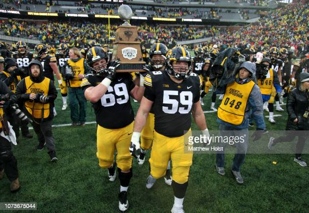 Offensive linemen Keegan Render and Ross Reynolds of the Iowa Hawkeyes carry the Heroes Trophy off the field after their matchup against the Nebraska...