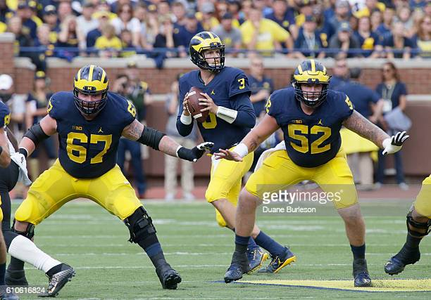 Offensive linemen Kyle Kalis of the Michigan Wolverines and Mason Cole of the Michigan Wolverines protect quarterback Wilton Speight of the Michigan...