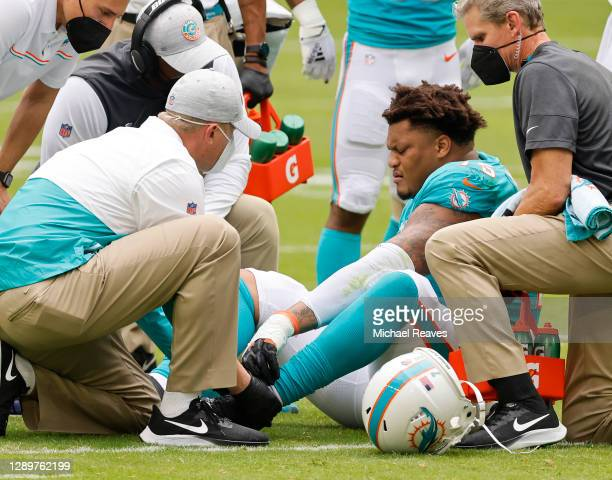 Offensive tackle Ereck Flowers of the Miami Dolphins is attended to by team trainers on the field after suffering an injury in the first quarter of...