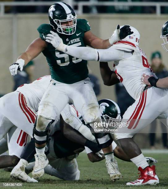 Offensive tackle Jordan Reid of the Michigan State Spartans defends against defensive lineman Willington Previlon of the Rutgers Scarlet Knights...