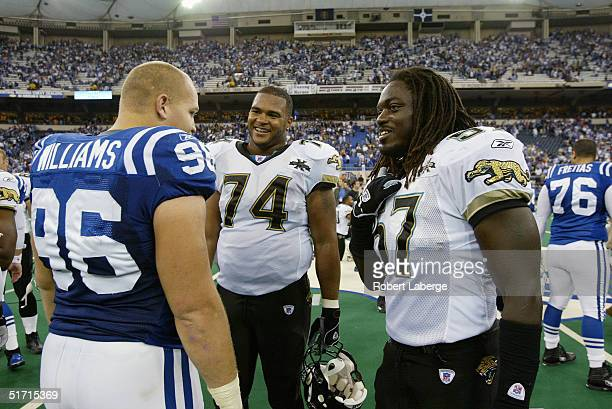 Offensive tackle Maurice Williams and linebacker Tommy Hendricks of the Jacksonville Jaguars talk to defensive tackle Josh Williams of the...