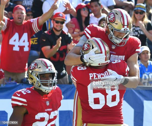 Offensive tackle Mike Person celebrates with running back Matt Breida and tight end George Kittle of the San Francisco 49ers after a touchdown in the...