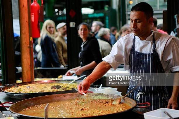 offering a sample of a curry in Borough Market, London