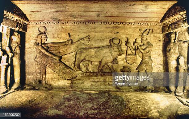 Offering scene with the sacred bull Apis The dead man is offering to the bull while Isis behind spreads her wings in protection Apis served as the ba...