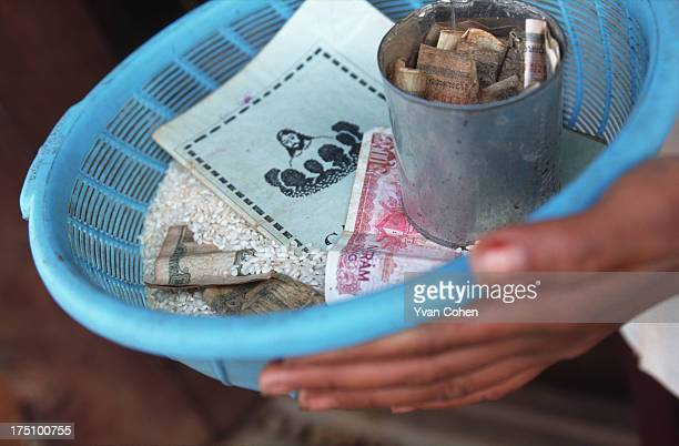 BOUSRA MONDOLKIRI CAMBODIA Offerings being collected during a catholic mass in a small Phnong montagnard village in northeastern Cambodia...