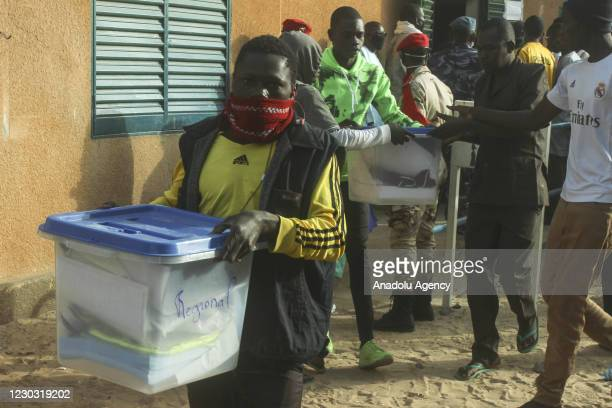Officals carry ballot box as voting for presidential and parliamentary elections is underway in Maradi, Niger on December 27, 2020.