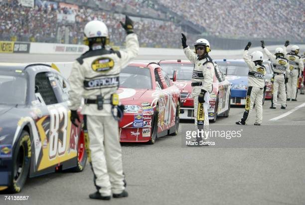 Officals hold up their hands to signal that the drivers are ready to start the race, prior to the NASCAR Nextel Cup Series Dodge Avenger 500 on May...