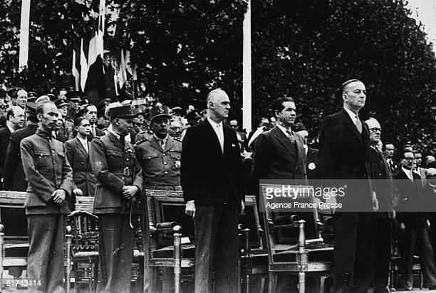 Officals stand as they watch a military parade Paris France July 14 1946 From left Ho Chi Minh Generals Jean De Lattre Tassigny and AlphonsePierre...