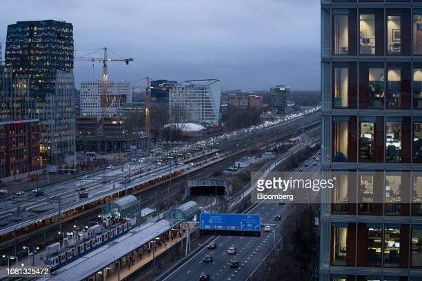 Office and commercial property stand along a highway and railway lines at dusk in the Zuidas financial district in Amsterdam Netherlands on Friday...