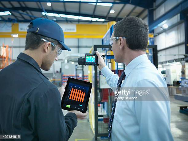 Office and factory worker using digital tablet and infra red camera to check power use in factory