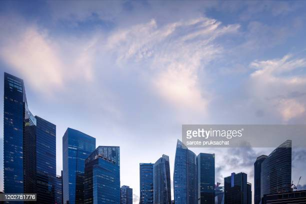 office and residential skyscrapers on bright sunset. - singapore cbd stock pictures, royalty-free photos & images