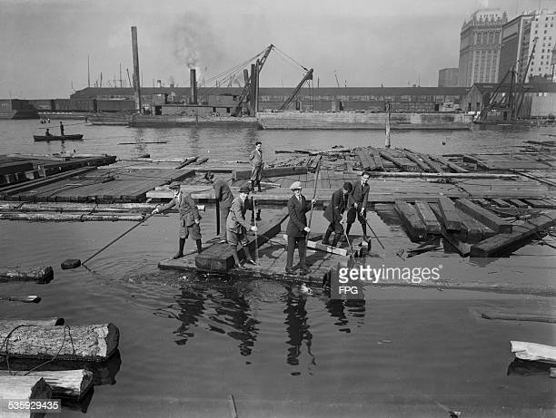Office boys from the nearby Whitehall Building messing about on rafts on the Hudson River near Battery Park lower Manhattan New York City October 1924