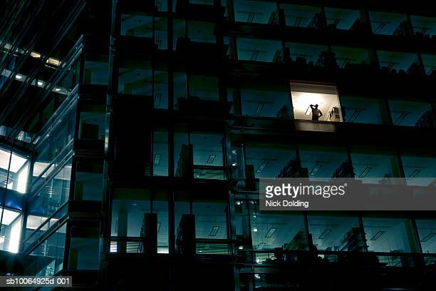 office building at night, man standing in one illuminated window, low angle view - bürogebäude stock-fotos und bilder