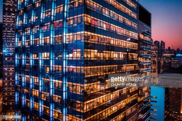 bürogebäude nachts mit beleuchteten fenstern - hauptfirmensitz stock-fotos und bilder