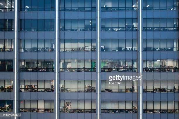 office building facade at night - 996 working hour system stock pictures, royalty-free photos & images