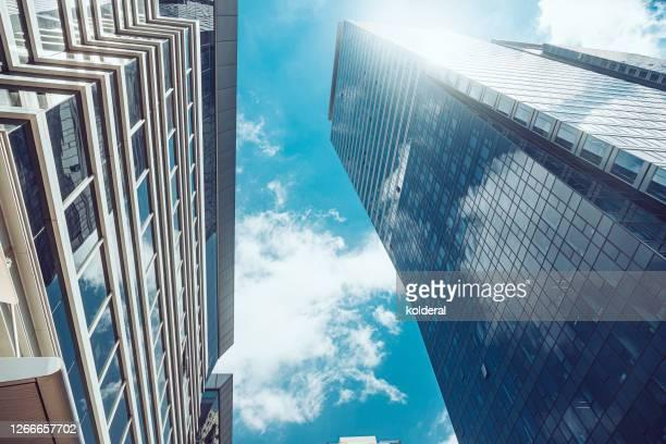 office buildings against blue sky - 商業不動産 ストックフォトと画像