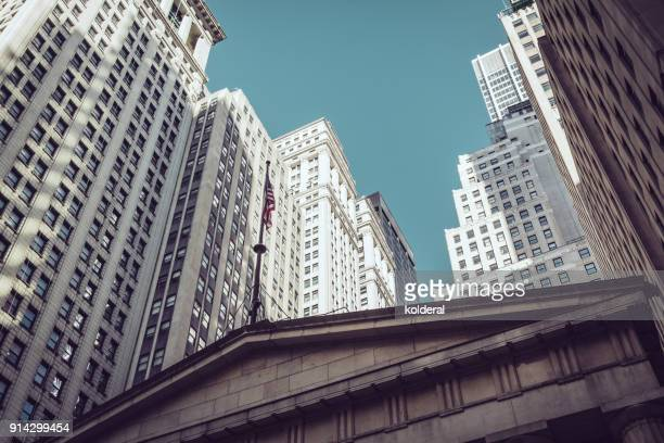 office buildings next to federal hall national memorial with statue of george washington on wall street - wall street stock photos and pictures