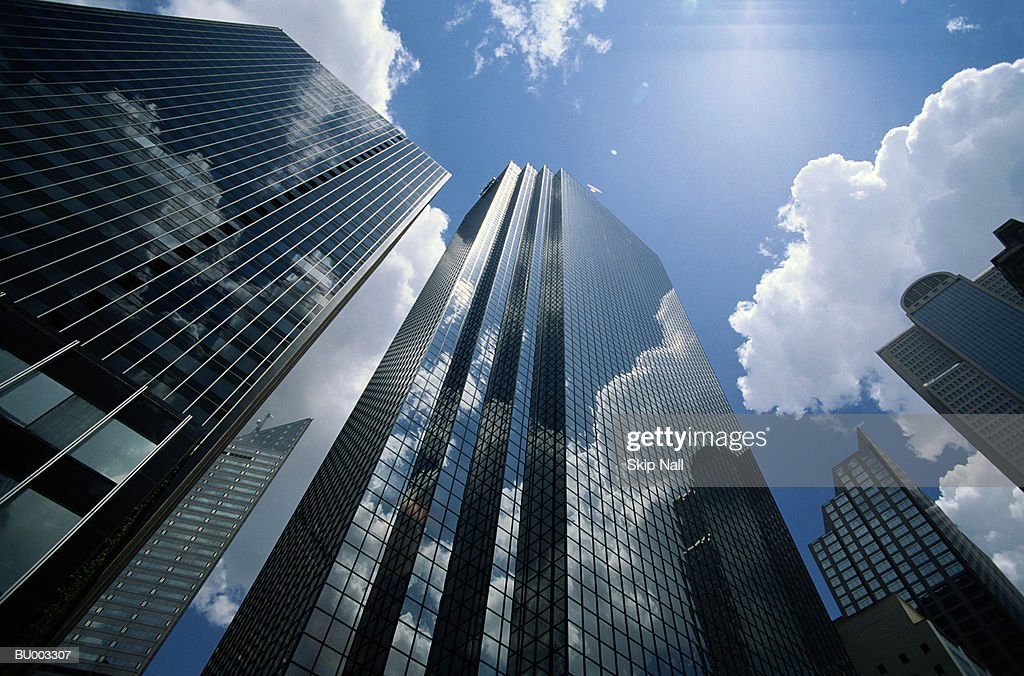 Office buildings reflecting clouds, low angle view : Stock Photo