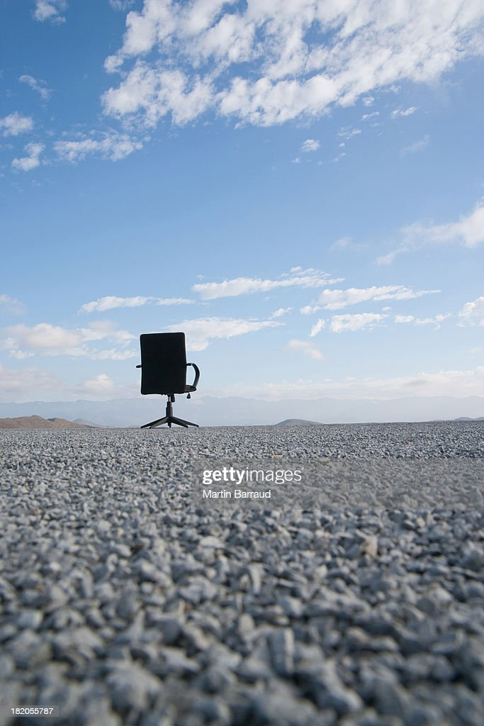 Office chair on a terrain full of pebbles : Stock Photo