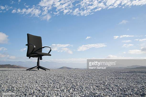 Office chair on a terrain full of pebbles