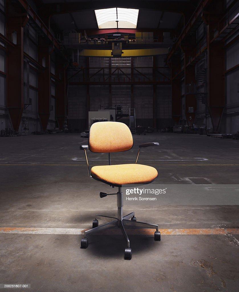 Office Chair Under Spotlight In Empty Warehouse Stock Photo ...