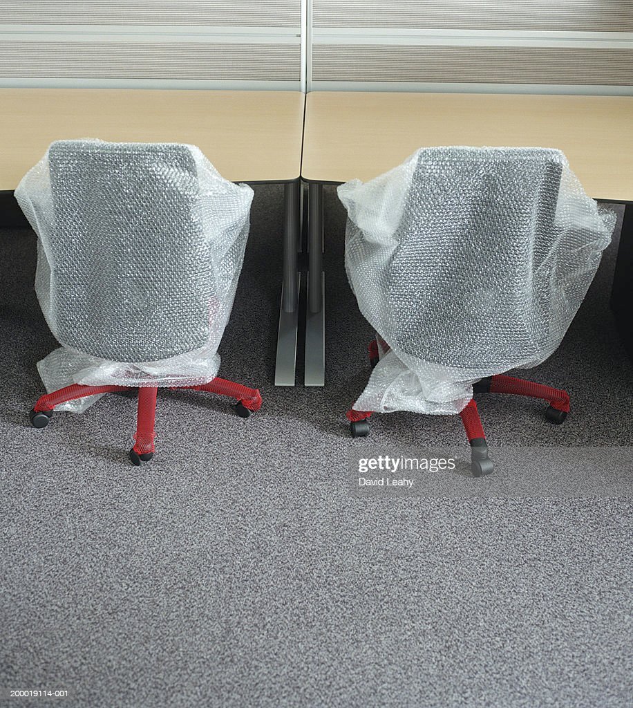 Office Chairs Covered In Bubble Wrap At Desks : Stock Photo
