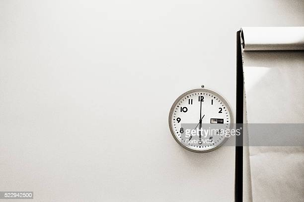 office clock beside writing pad - vcg stock pictures, royalty-free photos & images
