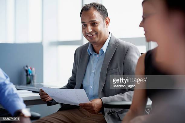 Office colleague talking during business meeting