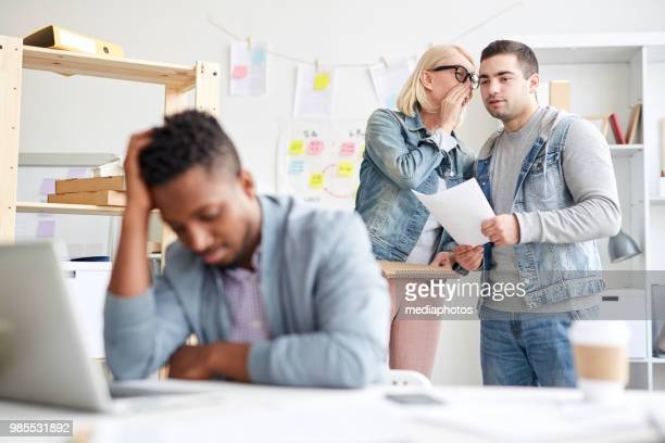 Office colleagues gossiping about new employee: attractive lady in casual clothing holding sketchpad and whispering secret to friend about failed black intern in office