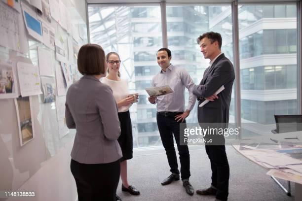 colleghi di ufficio che parlano nello studio di pianificazione dell'agenzia di progettazione - concorso foto e immagini stock
