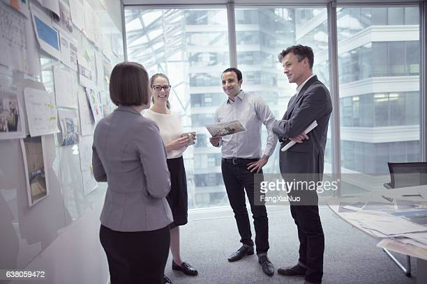 Office colleagues talking in design agency planning studio