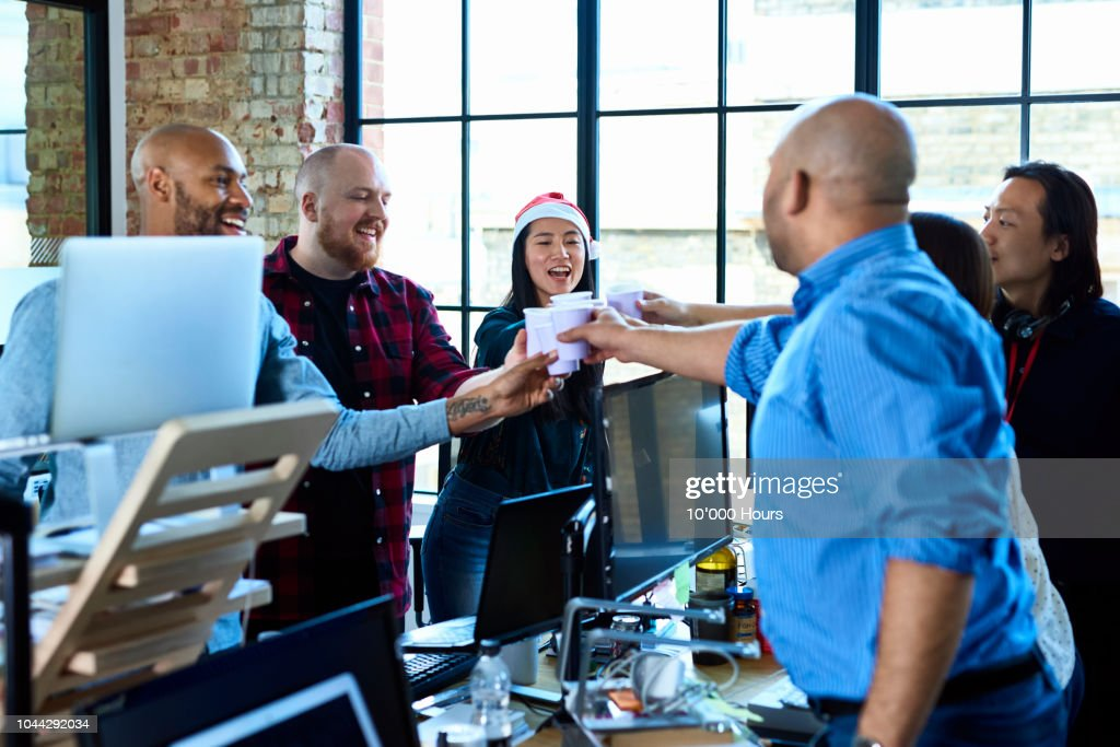 Office colleagues toasting at work with plastic cups : Stock Photo