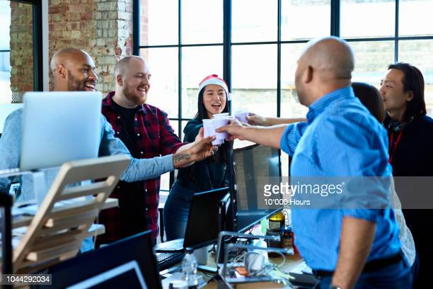 office colleagues toasting at work with plastic cups - work party stock pictures, royalty-free photos & images