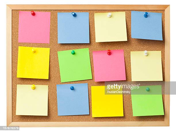 Office cork board full of colored memo notes.