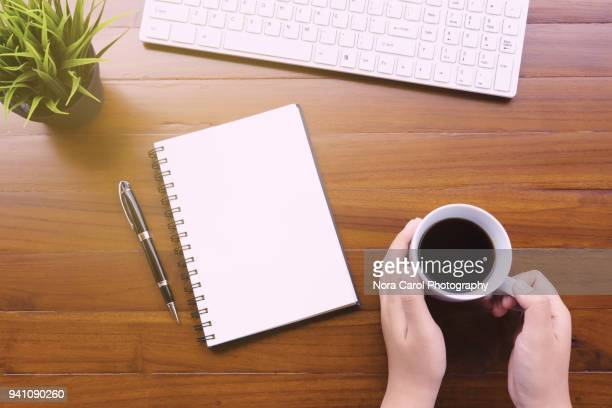 office desk and hands holding cup of coffee - office desk top view stock photos and pictures