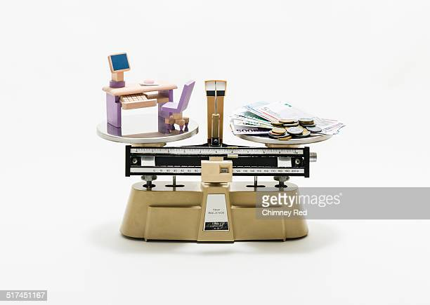 Office desk & money balanced on industrial scales