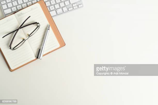 office desk table top view with computer keyboard, small notebook and isolated white background with copy space - datortangent bildbanksfoton och bilder