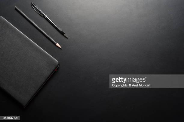 office desk table with note pad, pen, pencil on black background, top view with copy space - accessoires stock-fotos und bilder