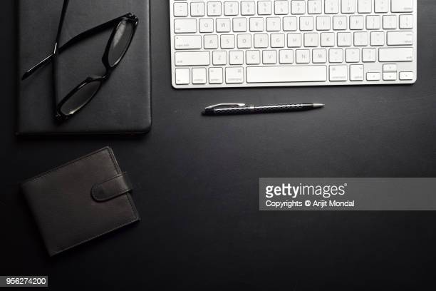 Office Desk Top View with Wallet, Keyboard, Pen, Diary, Eyeglasses on Black Background with Copy Space