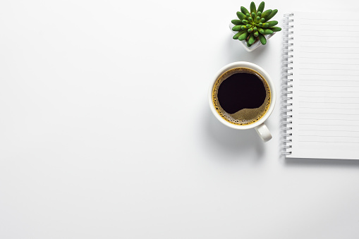 Office desk with coffee cup, cactus pot and blank notebook 1043725222