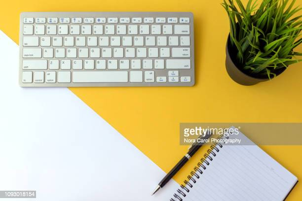 office desk with computer keyboard and note pad - computer keyboard stock pictures, royalty-free photos & images
