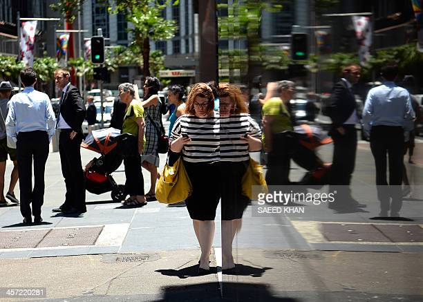 Office employees are reflected in the Reserve Bank of Australia's wall in the central business district of Sydney on December 17 2013 Australia is...