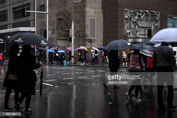 Office employees brace the rain during their lunch time break in the central business district of Sydney on September 17 2019