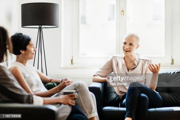 office employees taking break and talking - mitarbeiterengagement stock-fotos und bilder