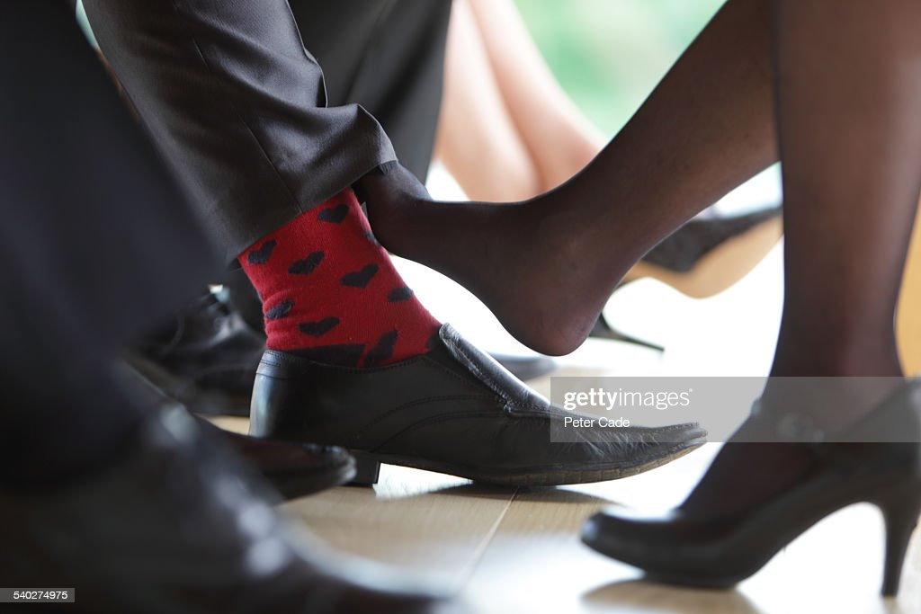 office environment , playing footsie. : Stock Photo