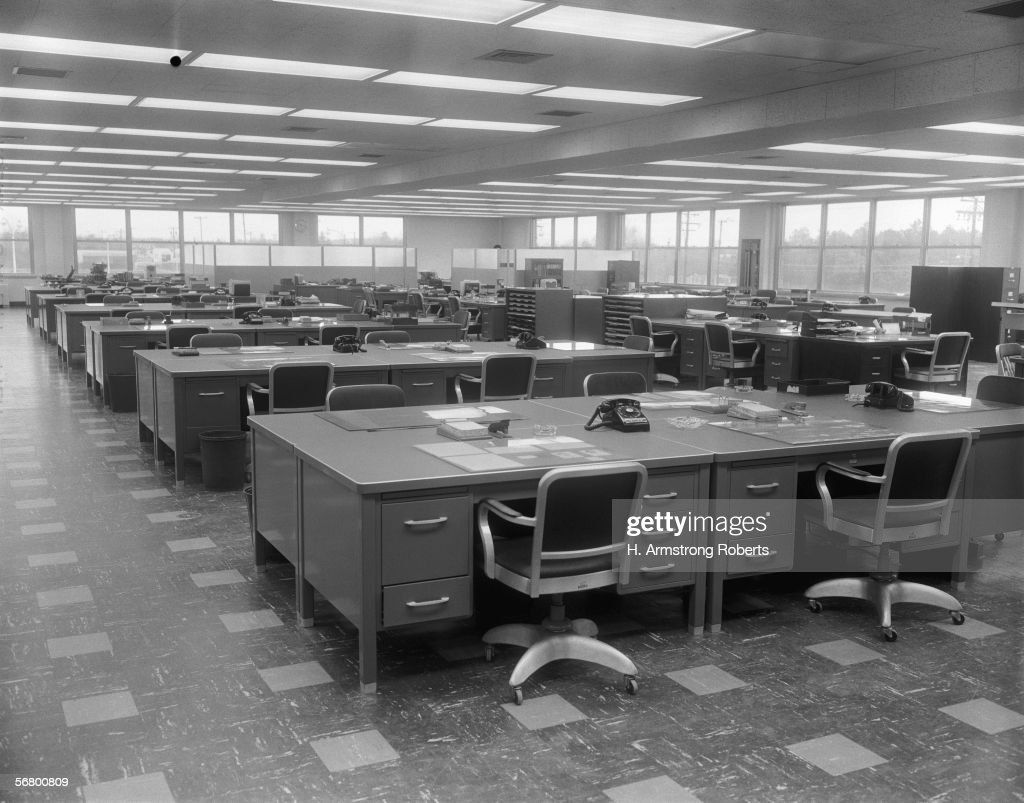 Office interior with metal desks, swivel chairs and black phones.